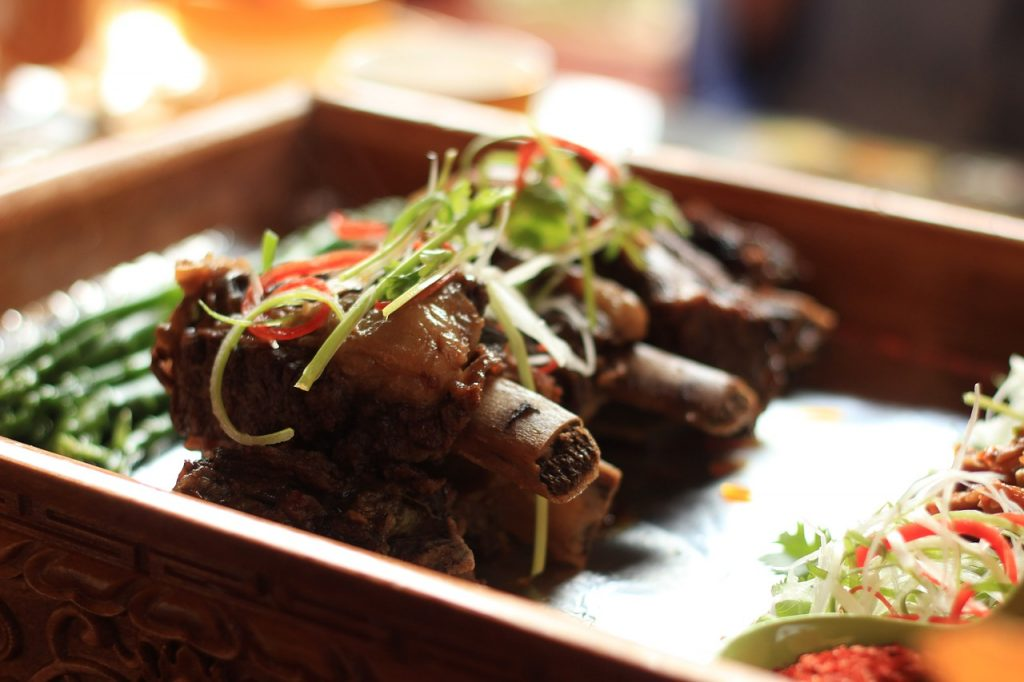 Things to do in Tibet: Eat yak meat dish with vegetables on Barkhor Street in Lhasa, Tibet.