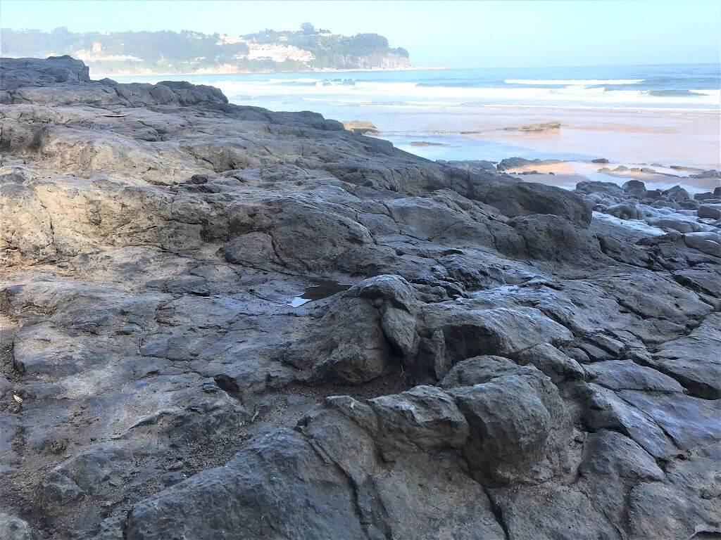 Dinosaur footprints with Llastres fishing village in the background