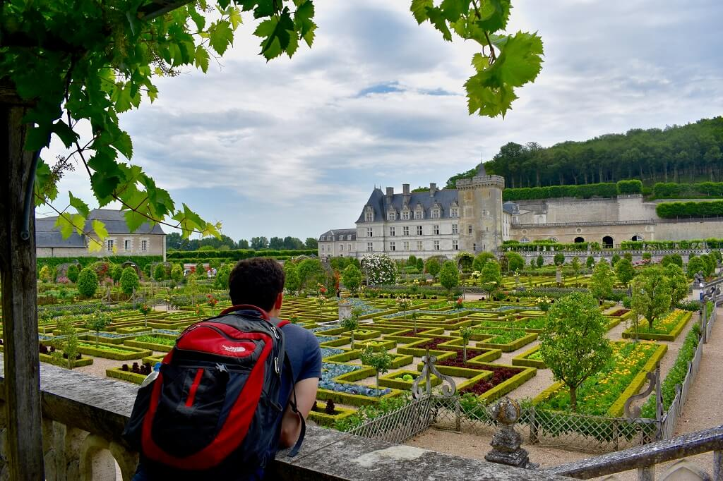 Nomadic Matt in front of French castle overcoming obstacles to travel