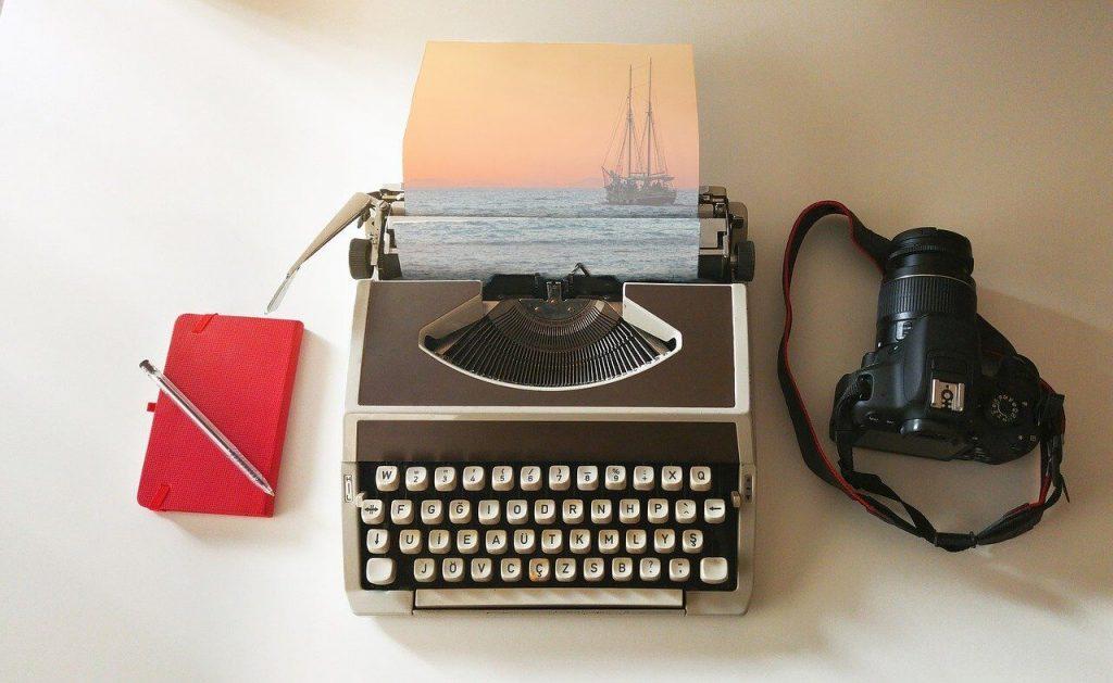 red travel journal, typewriter and camera